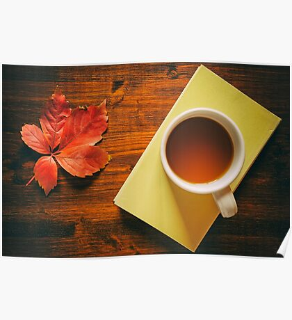Cup of tea on a book and autumnal leaf Poster