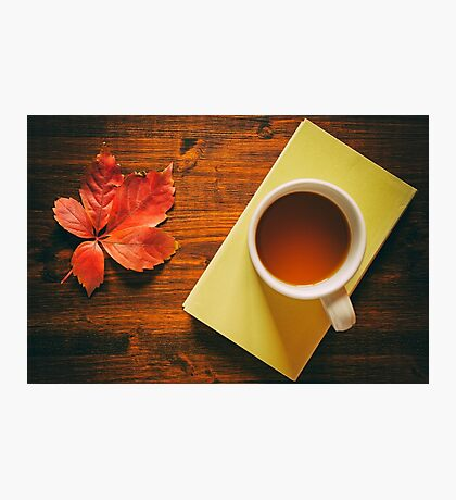 Cup of tea on a book and autumnal leaf Photographic Print