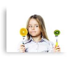 Funny little girl selecting between kiwi and orange, isolated on white background Canvas Print