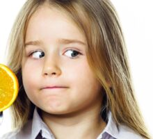 Funny little girl selecting between kiwi and orange, isolated on white background Sticker