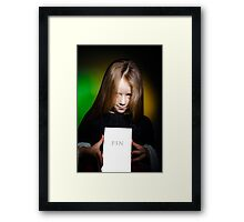 Cute little girl with long hair showing book, on colorful background Framed Print