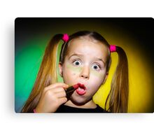Funny little girl making make-up by herself, on colorful background Canvas Print