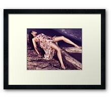 Young woman in dress lying on driftwood on a shore art photo print Framed Print
