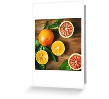 Different sort of orange fruit on wooden table Greeting Card