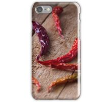 Colorful chili peppers on wood background iPhone Case/Skin