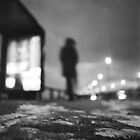 Man waiting at bus stop at night in winter square black and white analogue medium format film Hasselblad  photo by edwardolive