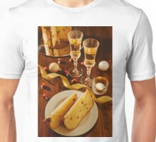 Sliced italian panettone, sparkling wine and decorations over a table Unisex T-Shirt