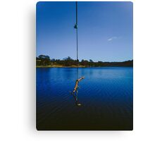 Rope swing on a lake Canvas Print