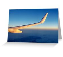 Wing of flying Boeing 737-800 against evening sky Greeting Card