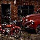 Indian 101 Scout and Chevy truck at a garage by Frank Kletschkus