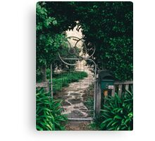 Leafy gate with a bicycle wheel decoration Canvas Print