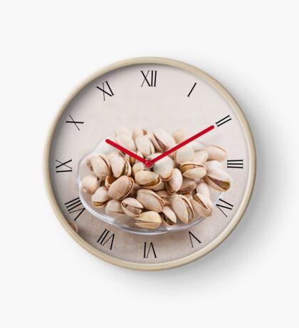 Pistachio nuts in shells lying Clock