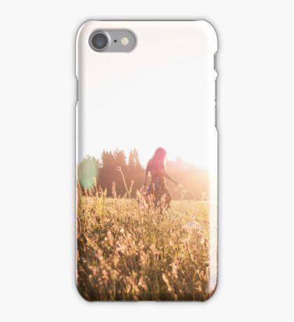 Woman walking through meadow at sunset iPhone Case/Skin