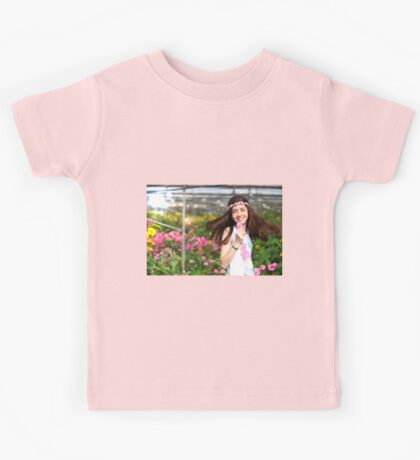 Young preteen girl of 12 in white dress in a hothouse of pink flowers  Kids Tee