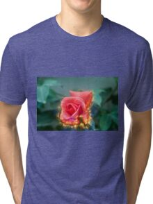 Digitally enhanced orange rose flower with green foliage background  Tri-blend T-Shirt