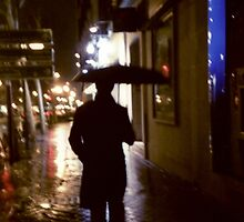 Man walking in street at night in rain color 35mm analogue photojournalism portrait photograph by edwardolive