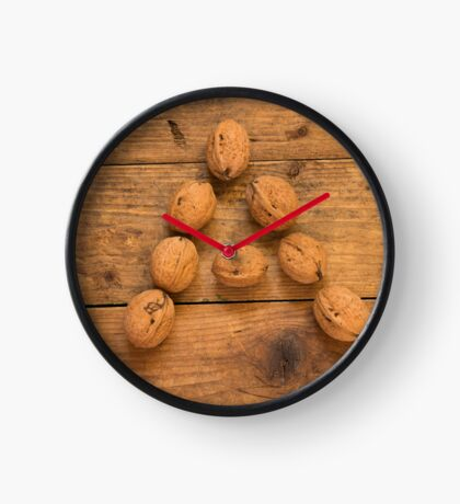 Letter A from walnuts on a wooden table. Clock