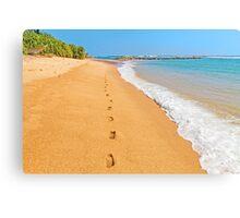 Footprints on sunny beach by emerald sea Canvas Print