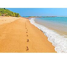 Footprints on sunny beach by emerald sea Photographic Print