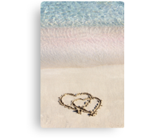 Two hearts drawn in the sand on a beautiful beach Canvas Print