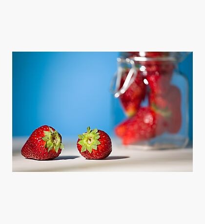 Close up of two strawberries on a table with blue background Photographic Print