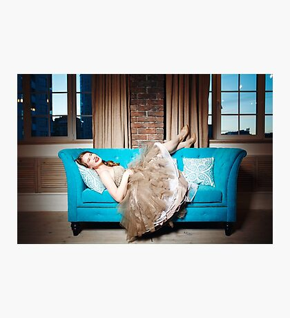 Beautiful Laughing Woman Lying on Blue Couch Photographic Print