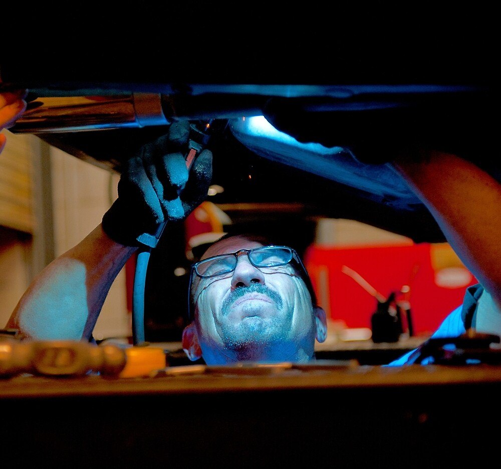 Mechanic soldering a muffler by Eyal Nahmias
