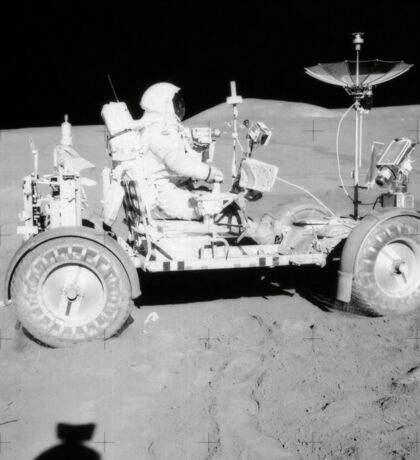 Astronaut is seated in the Lunar Roving Vehicle during an Apollo moonwalk. Sticker