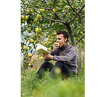 Teenager reading a book in the orchard Photographic Print