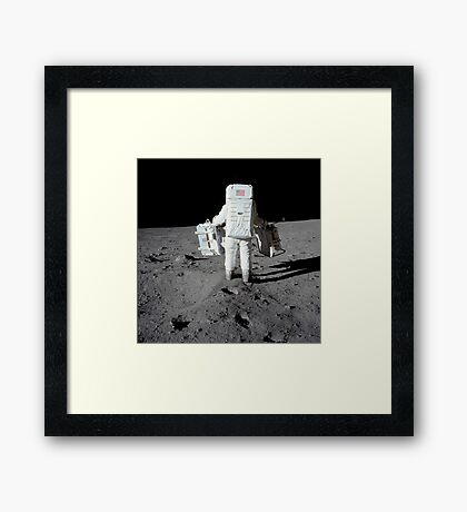 Astronaut carrying equipment to the deployment site on the moon. Framed Print