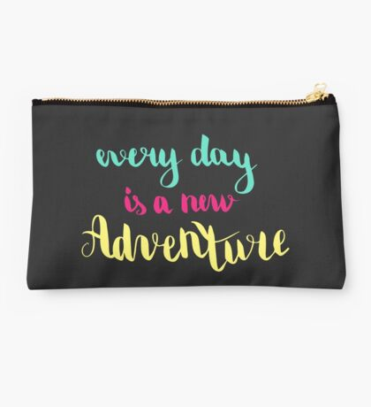 Every day is a new adventure. Colorful text on dark background. Studio Pouch