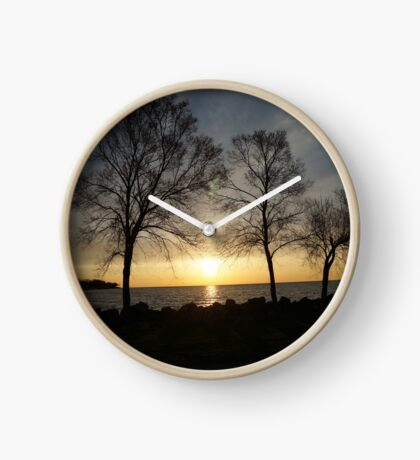Tree on a lake in a sunset Clock