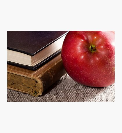 Detail of old books in hardcover and close-up red apple Photographic Print