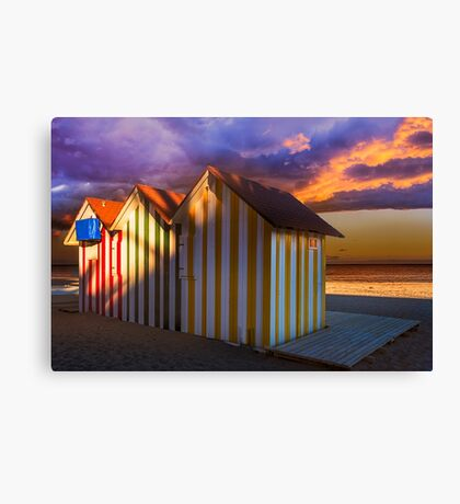 Beach huts and stormy sky at sunset Canvas Print