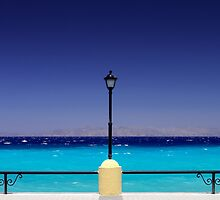 Turquoise sea with dark blue sky and a pylon in Greece by cannedmoods