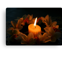 Candle surrounded by frangipanis Canvas Print