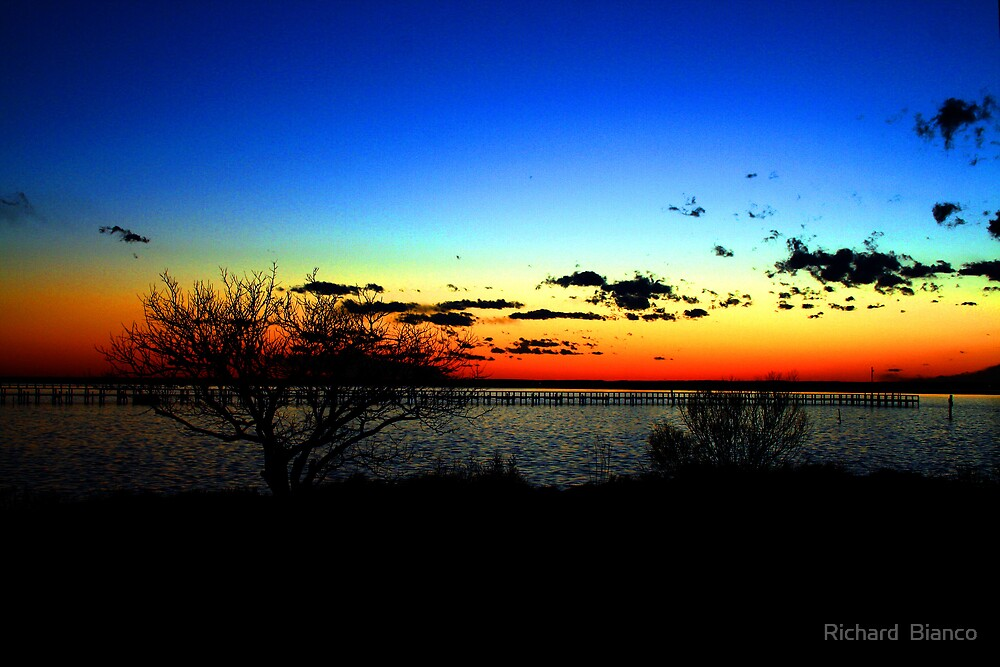 Sunset over Chincoteague Inlet. by Richard  Bianco