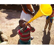 African child plays with toy horn Photographic Print