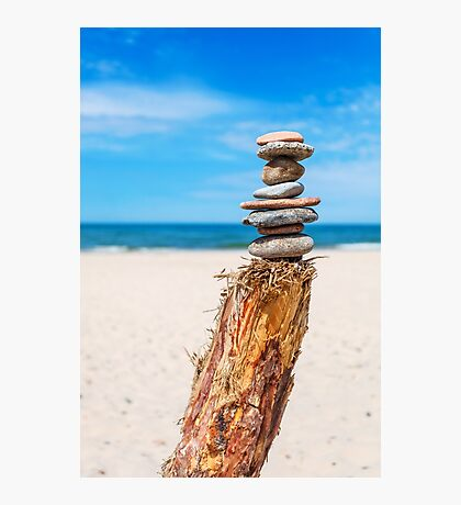 Stack of stones on the beach against blue sky Photographic Print