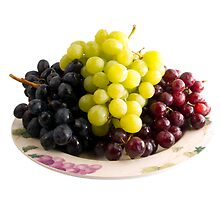 fresh red, black and white grapes on a plate by travis manley