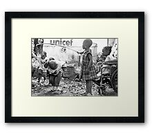 Street kids playing 'skippy' with disused iron bar, Democratic Republic of Congo Framed Print