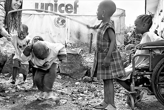 Street kids playing 'skippy' with disused iron bar, Democratic Republic of Congo by Melinda Kerr