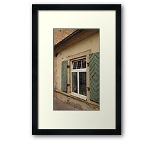 Dog is looking through a window of the house. Framed Print