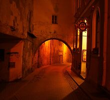 Old Town building's arch at night. by miniailov
