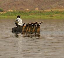 Man in a tin boat crossing the Zambezi River by Sandra Kent