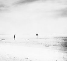 Man and woman are walking on the beach by Olja Merker