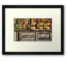 Mantle with a collection of bottles Framed Print