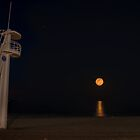 Lifeguard tower greets an orange moon by Ralph Goldsmith