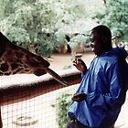 Charles feeding Giraffe  by John Hansen