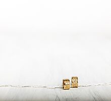 Golden wedding rings on white wooden background  by PhotoStock-Isra